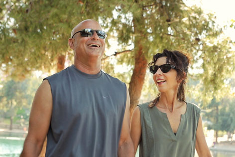 Cary and Catherine Goronkin stroll around a lake in Fullerton as part of his health regimen to keep Crohn's disease in check